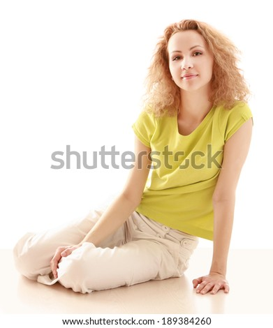 A young woman sitting on the floor, isolated on white - stock photo