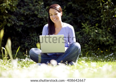 A young woman sitting on the grass, using a laptop