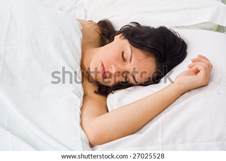 A young woman sleeping in bed alone