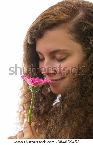 A young woman smelling a pink flower with eyes closed
