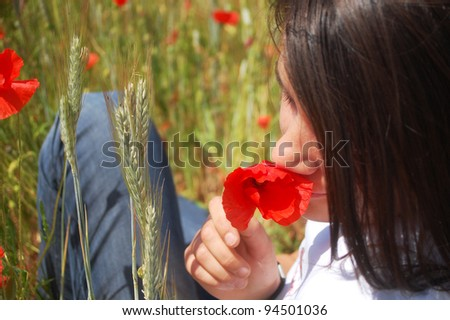 A young woman smelling a wild red poppy.