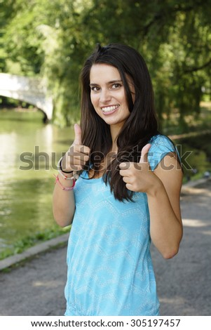 A young woman smiles and gives thumbs up.