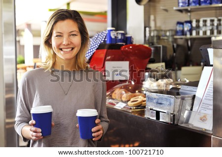"a young woman smiles to camera as she walks away from the cafe counter carrying her two coffees, part of my ""cafe girl"" series - stock photo"