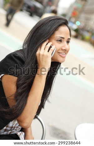 A young woman smiling as she chats on the phone outdoors.