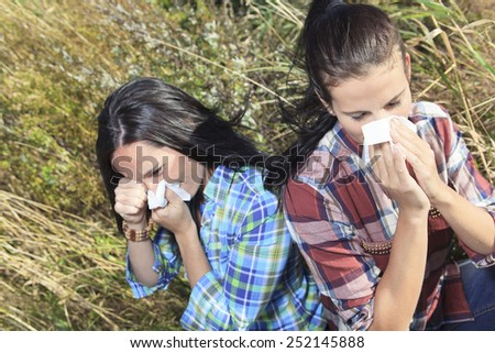 A Young woman sneezing in a field. Concept: seasonal allergy. - stock photo