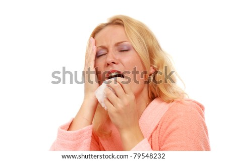 A young woman sneezing, isolated on white