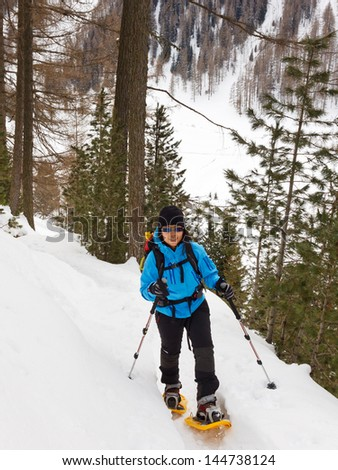A young woman snowshoeing in the Alps,  South Tyrol, Italy - stock photo