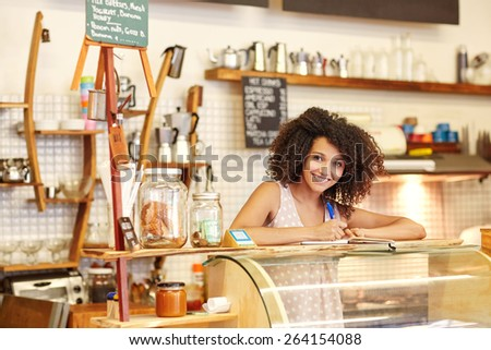 A young woman standing behind the counter in a coffee shop - stock photo