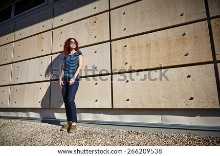 a young woman standing in front of a modern wall - stock photo