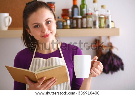 A young woman standing in her kitchen drinking tea and holding a cookbook. - stock photo