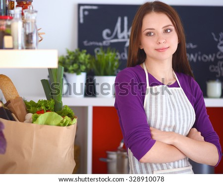 A young woman standing in her kitchen with bag of groceries in the background. - stock photo