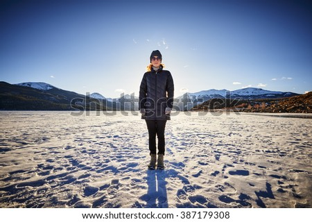 a young woman standing on a frozen mountain lake at sunset - stock photo