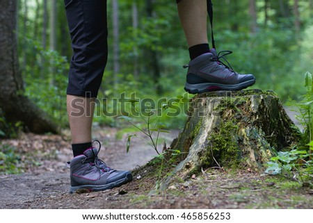 A young woman standing on a tree stump in the middle of forest trail, hiking boots in focus