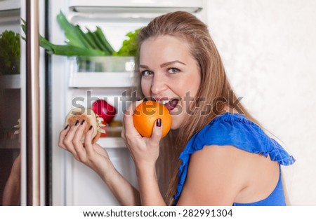 a young woman stands at the fridge and selects between an orange and a hamburger