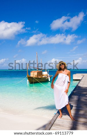 A young woman stands on a pier - stock photo