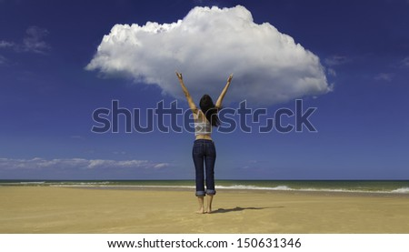 A young woman stands on a sandy beach, as if commanding the clouds, rainmaking/ Young woman on beach facing cloud