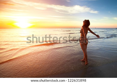 A young woman stands on the beach during a beautiful sunset, vacation vitality healthy living concept. - stock photo
