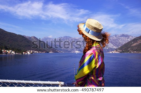 A young woman stands on the ship deck and watching the sea and mountains. The red-haired girl in a hat and dress floating on a boat in the Adriatic Sea.