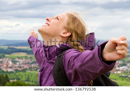 A young woman stands on top of a mountain peak, with her hands raised skyward - stock photo