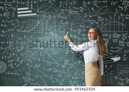 A young woman stands smiling in front of a chalkboard filled with charts and graphs.