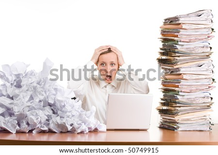 A young woman stressed at work with a pile of paperwork.