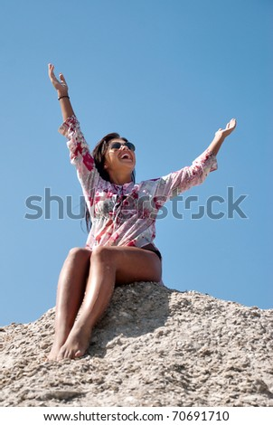 A young woman stretches her hand towards the sky - stock photo