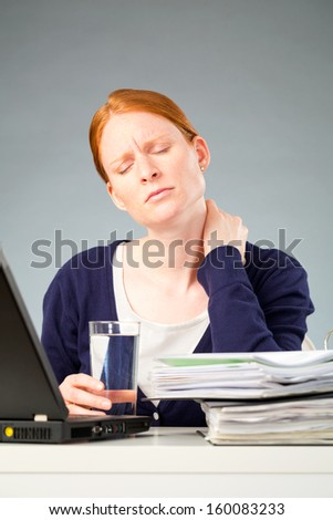 A young woman suffering from neck pain at work, sitting behind a desk with a computer and documents.