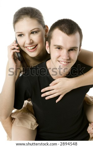 A young woman takes a call whilst on a guys back - stock photo