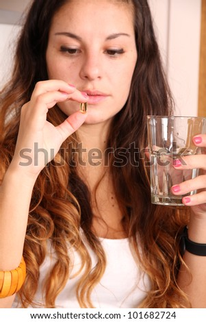 A young woman taking a pill with a glass of water. - stock photo