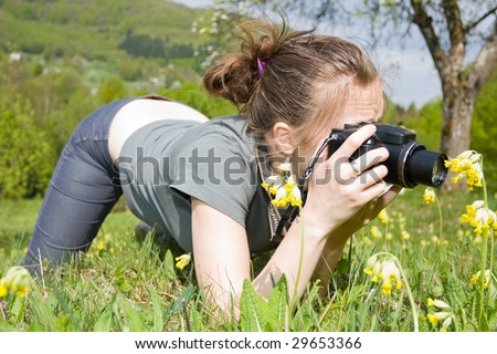A young woman taking photos of a flower. - stock photo