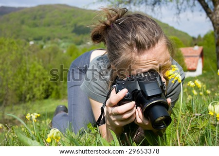 A young woman taking photos whit a compact digital camera outdoors. - stock photo