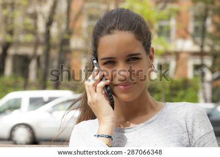 A young woman talking on a cell-phone. She is outdoors in a city with a brick building on the background and cars. Horizontal Shot. - stock photo