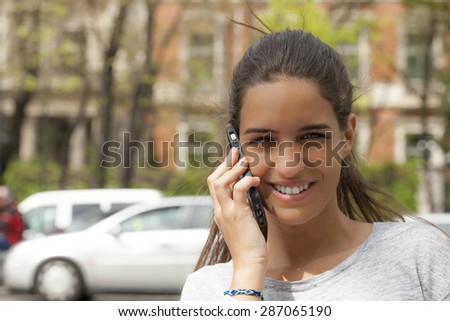 A young woman talking on a cell-phone with a smile. She is outdoors in a city with a brick building on the background. Horizontal Shot. - stock photo