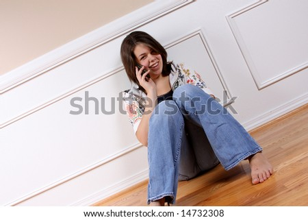 A young woman talking on her cell phone, sitting on the floor. - stock photo