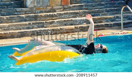 A young woman teenager having fun in a swimming pool in Europe