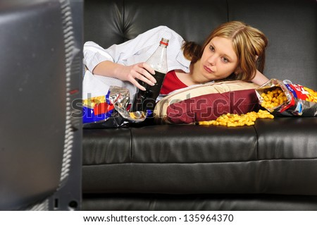 A young woman, teenager with long blond hair lolls on a black leather sofa, watching television and eating crisps and coke here. - stock photo