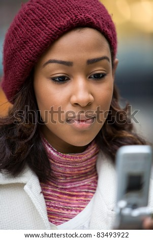 A young woman text messaging or checking email on her wireless phone. Shallow depth of field. - stock photo