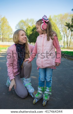 A young woman to prepare a little girl to ride on roller skates
