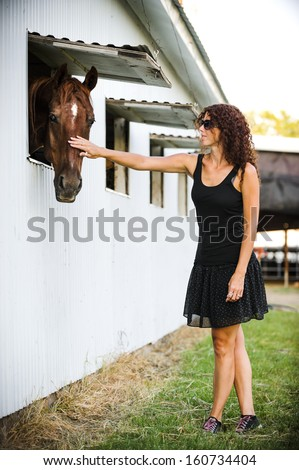 a young woman touching a horse.  the horse is looking at the camera. - stock photo