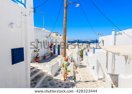 A young woman tourist standing on Mykonos town street looking at sea, Cyclades islands, Greece