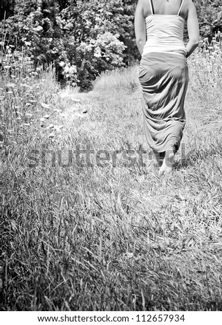 A young woman walking away along a nature path.