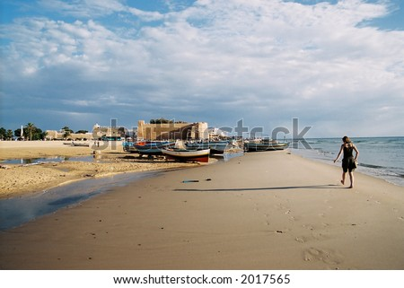 A young woman walking past fishing boats in the late evening light (Tunisia).