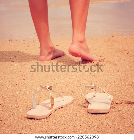 A young woman walks alone on a beach vintage filter. - stock photo
