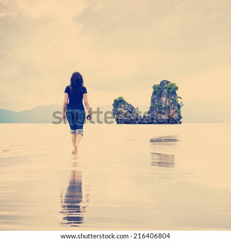 A young woman walks alone on a beach with Instagram style filter