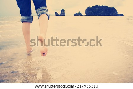 A young woman walks alone on a beach with Instagram style filter - stock photo