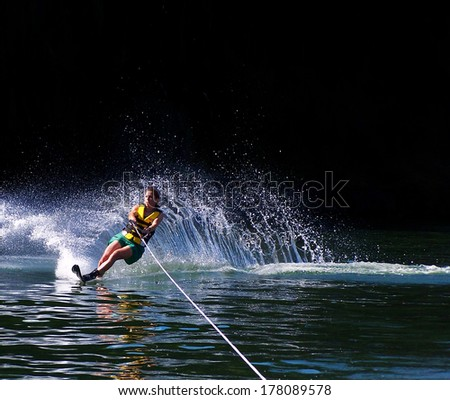 a young woman water skiing on a lake - stock photo