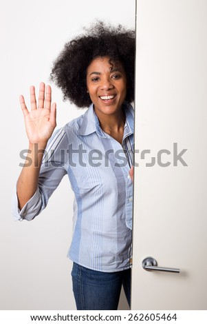 a young woman waving goodbye at the door. - stock photo