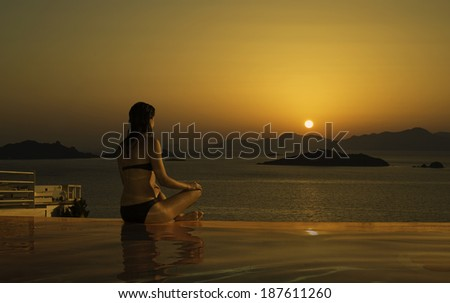 A young woman wearing a bikini sits meditating facing a sunset by an infinity pool - stock photo