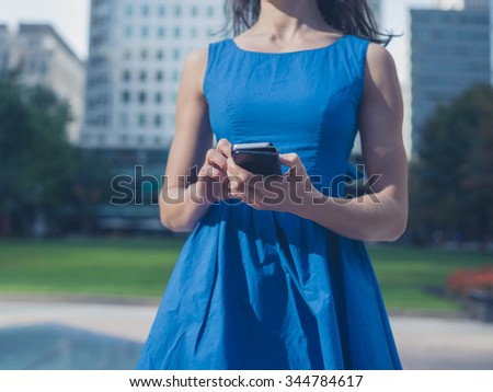 A young woman wearing a blue dress is standing in the city and is using a smart phone
