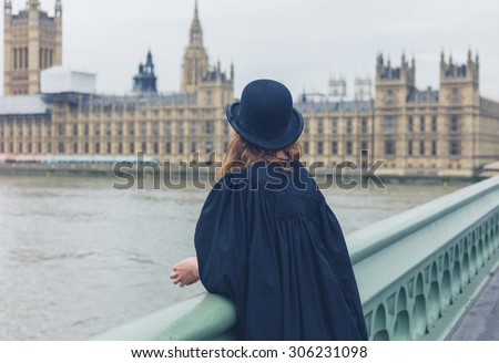 A young woman wearing a bowler hat and a graduation gown is standing on a bridge in London and is looking at the houses of parliament